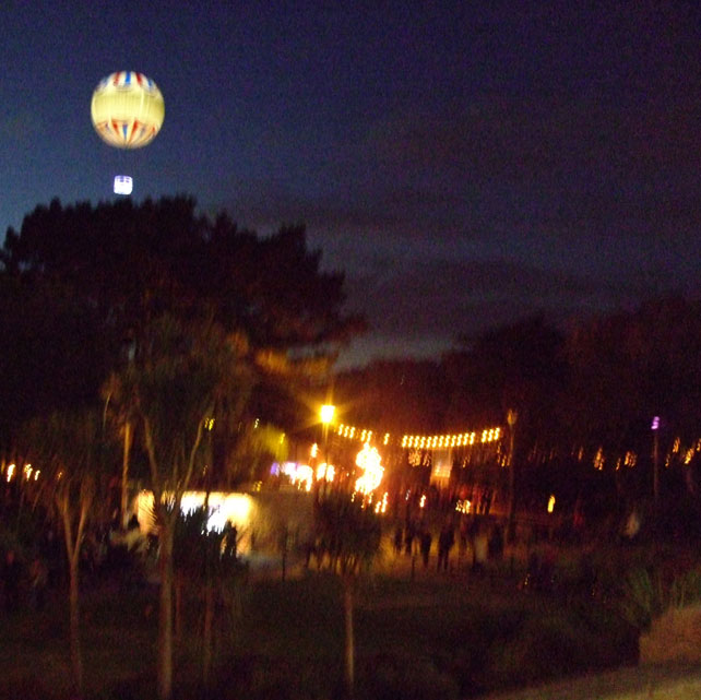 Bournemouth's hot air balloon suspended above the gardens, lit by fire installations