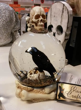 crystal ball containing a crow and with a skull on top