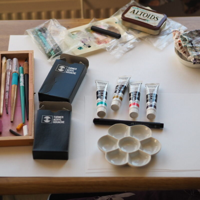 desk with paint tubes, a ceramic palette, a box of dip pens and other assorted art materials